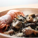Black risotto met bospaddenstoelen en grote garnalen