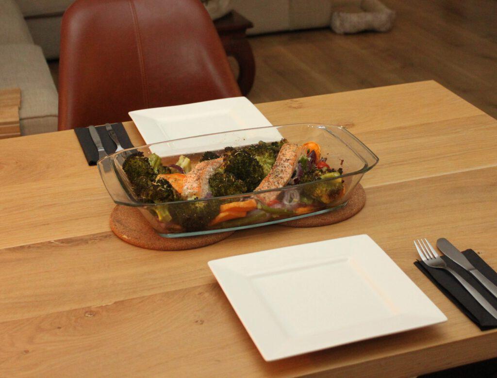 Aan tafel met de ovenschotel zalm, broccoli, tomaatjes en groene asperges