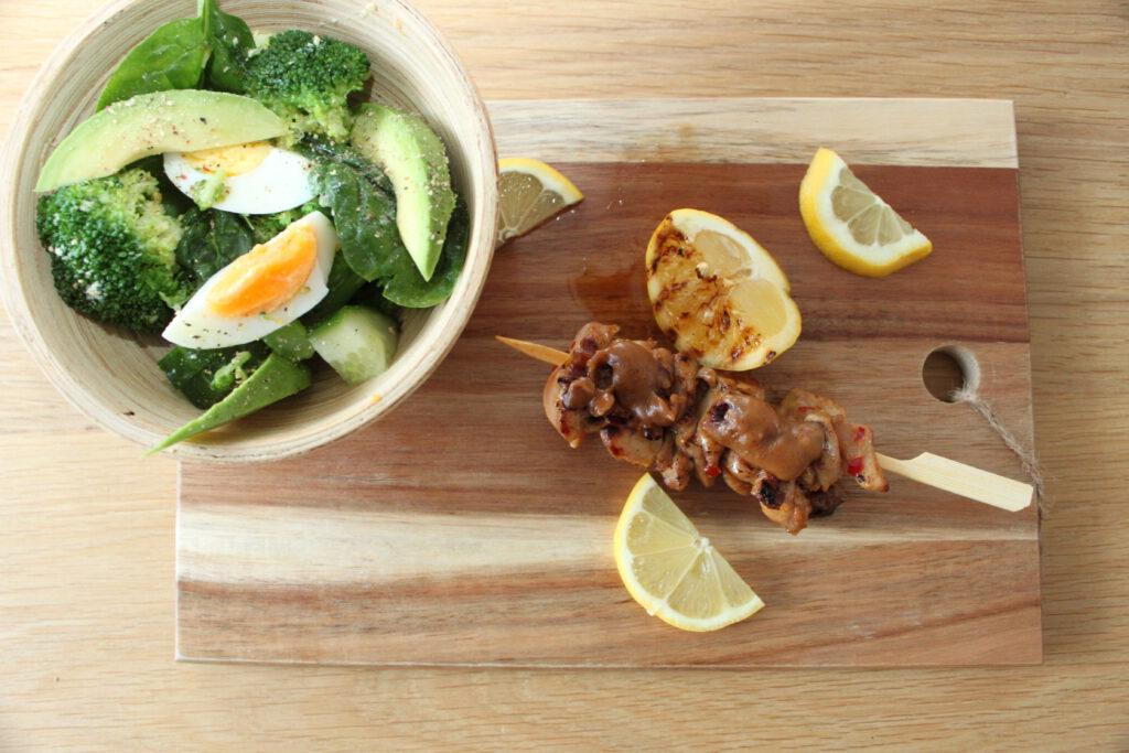 Bord met saté met satésaus en spinazie-broccolisalade